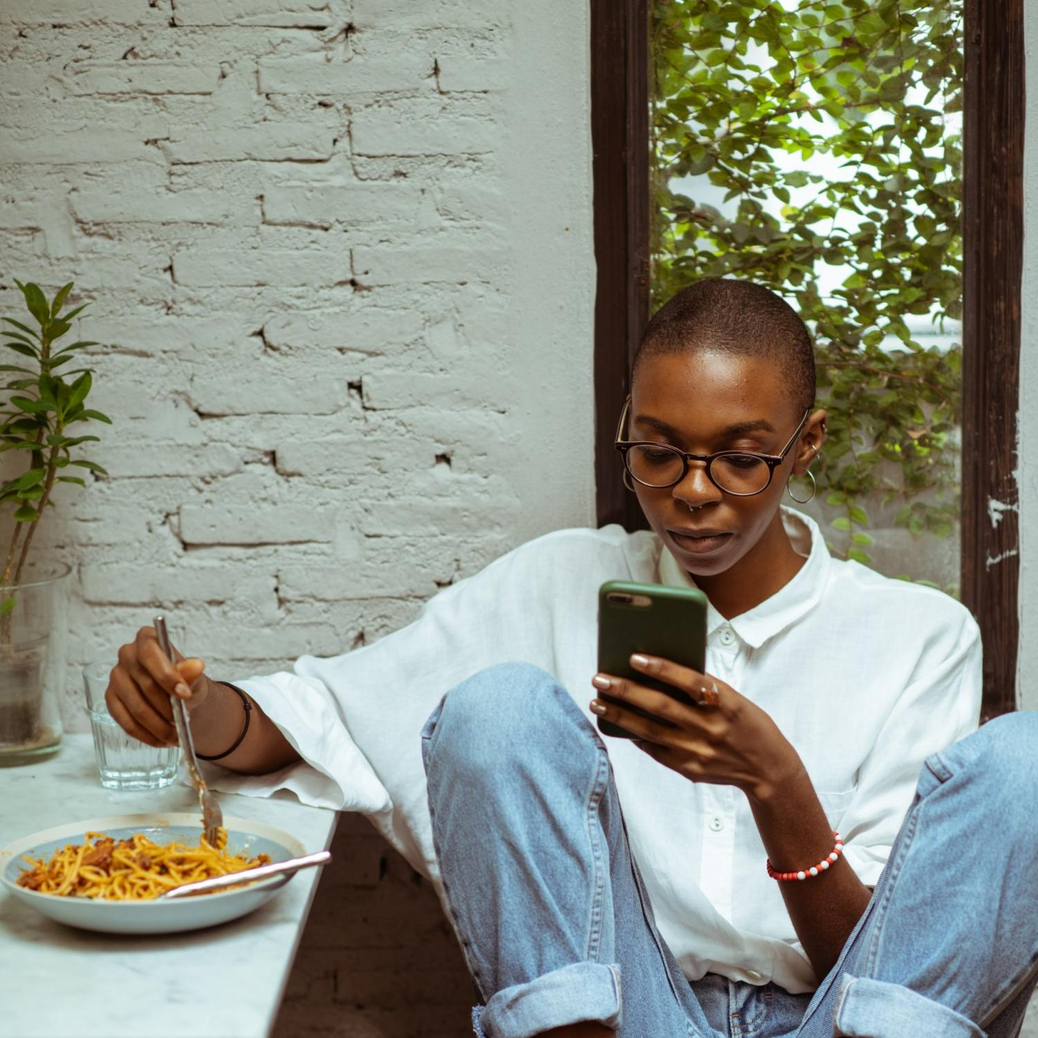 Student on Phone Eating Pasta