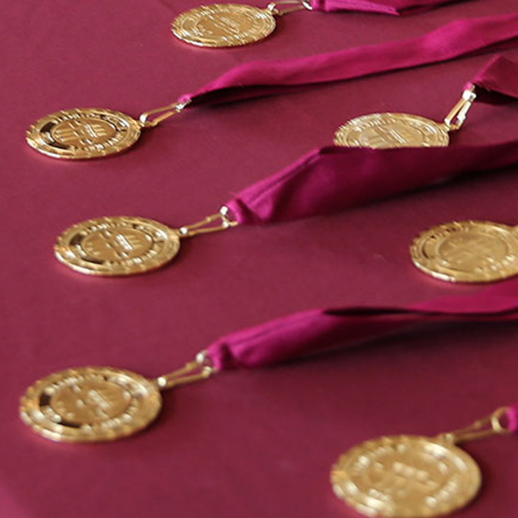 Image of Honors Medallions on garnet tablecloth. Also link to FSU News article on the number of Honors graduates for Spring 2021.